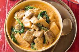 A creamy yellow curry with potato and beef chunks, as well as  bamboo slices and gai lan leaves