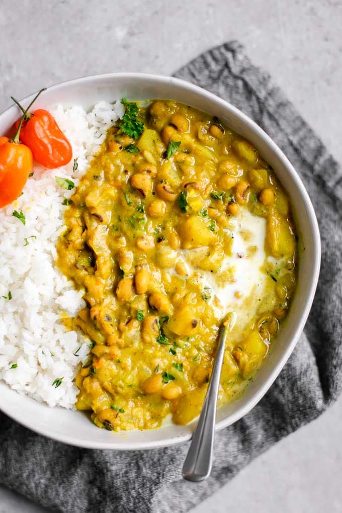 A bowl of yellow curry full of black eyed peas,  garnished with habaneros and a scoop of rice