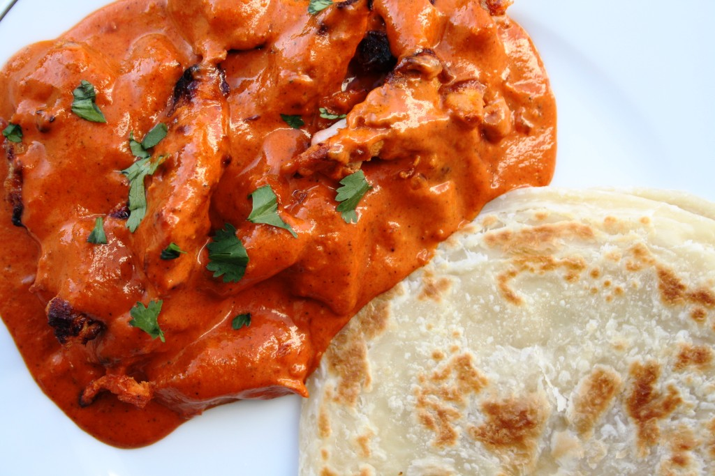 Butter chicken sitting in a bright red curry sauce with a parsley garnish