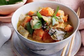 A soupy yellow curry with chunks of chicken and sweet potato, garnished with kaffir lime leaves