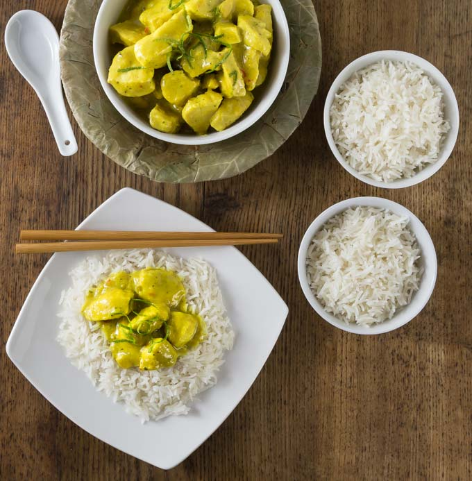 A yellow chicken amok curry on top of a bed of white rice