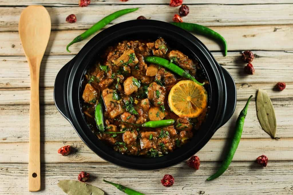 A chicken karahi curry with lemon, chicken , and green chilies
