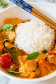 A orange panang curry, filled with chicken, kaffir lime leaves, red bell pepper and a big scoop of rice