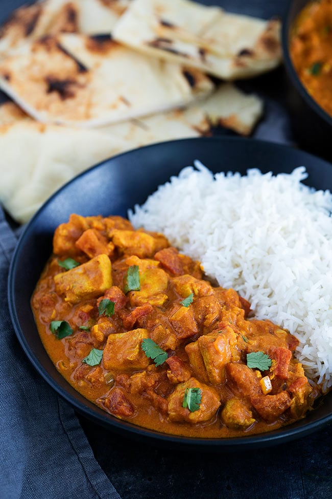 Chicken tikka masala, a orange curry with chunks of chicken and tomato