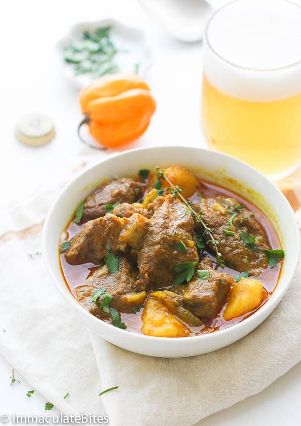 a red, soupy curry with large chunks of goat meat and potatoes