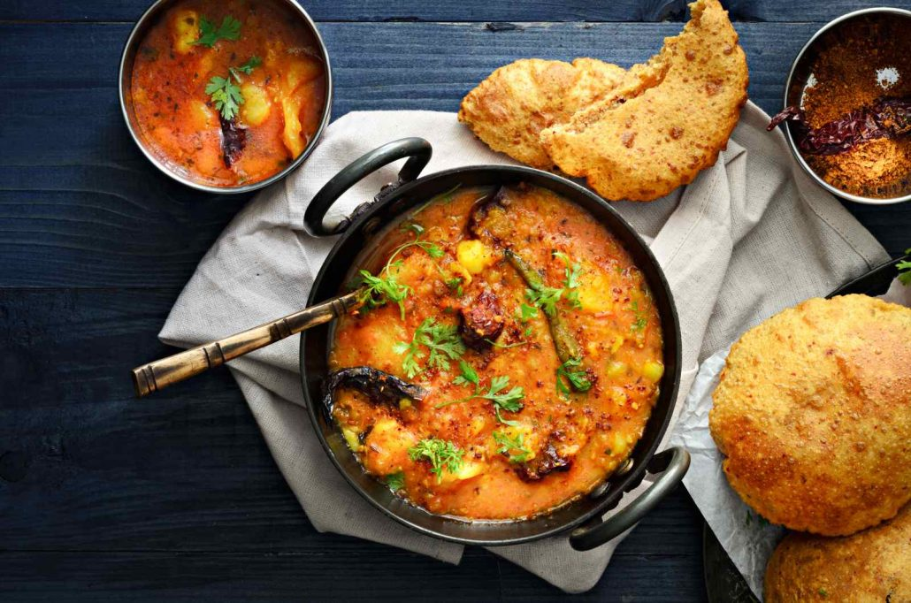 An orange curry, with potatoes as the focus, surrounded by tasty bread