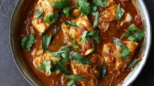 A red Durban fish curry, with fresh curry leaves and large chunks of white fish