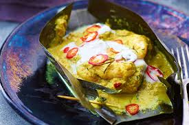 Fish steamed in a banana leaf with coconut cream, tomatoes, and a curry sauce