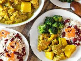 A yellow Jamaican curry with potaoes and chicken, with red beans, rice, and broccoli on the side
