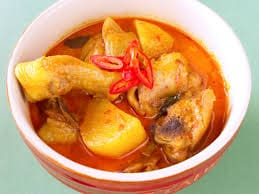 A soupy red curry broth, with chicken, potatoes, and red chili peppers