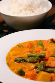 An orange curry with green beans, sweet potatoes, pumpkin, and carrots