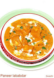 Bright orange curry with white cream, chicken cubes and a parsley garnish