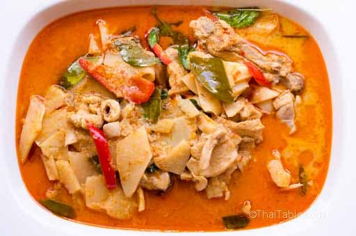 A orange curry with bamboo shoots, red bell pepper, kaffir lime leaves and thai basil
