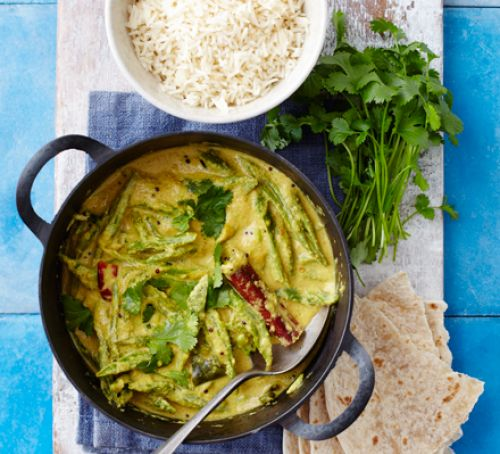 A bright green curry full of runner beans, coriander, and red chilies