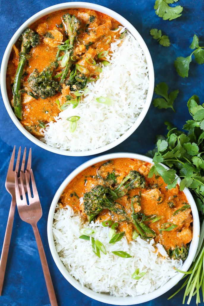 A big bowl of Thai red curry, filled with chicken, broccoli, scallions, and a big scoop of rice