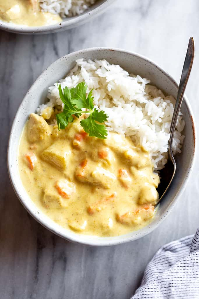 A yellow Thai curry with chunks of chicken and a big scoop of rice