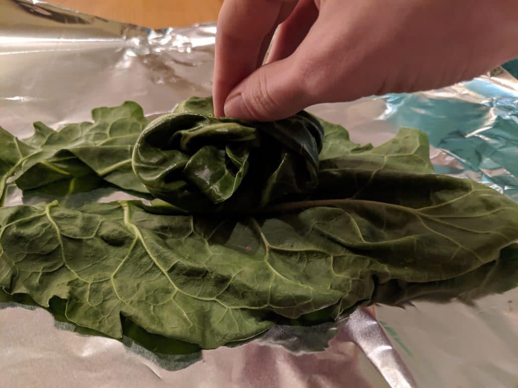 Swiss chard being folded with the filling inside of it. Aluminum foil on bottom.