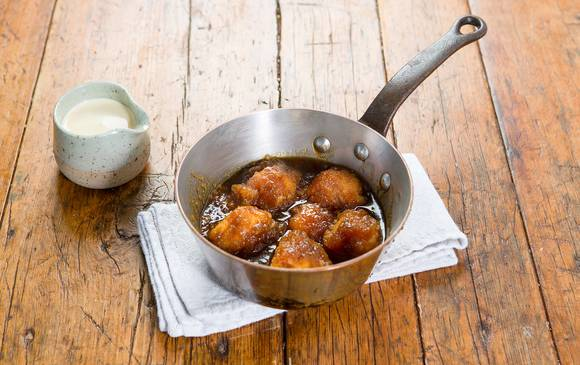 A steel pan with golden syrup dumplings and a side of vanilla cream
