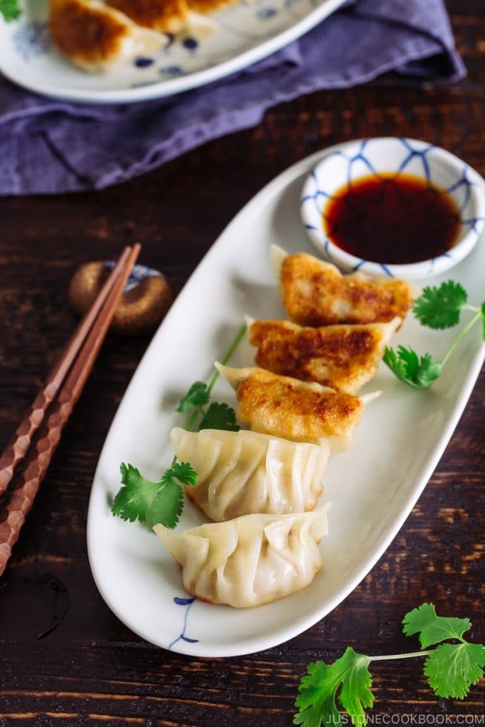 Crispy gyoza dumplings with a dipping sauce on the side