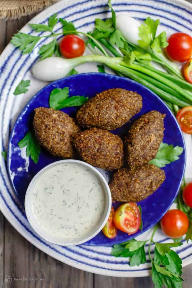 Crunchy oval shaped dumplings called kibbeh with a tzatziki sauce
