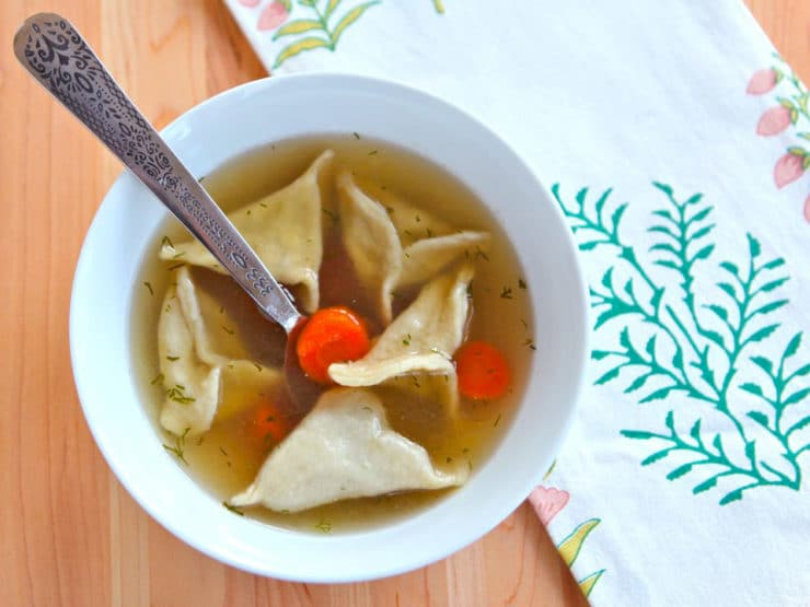 Triangular dumplings in a chicken soup with carrots