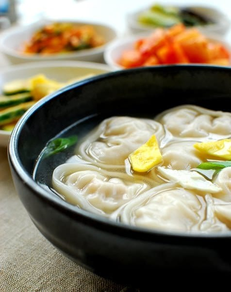 A clear soup broth with mandu dumplings added