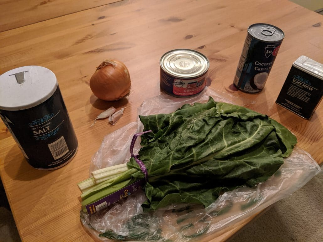Ingredients laid out: Swiss chard, salt, onion, garlic, corned beef, coconut cream, pepper.