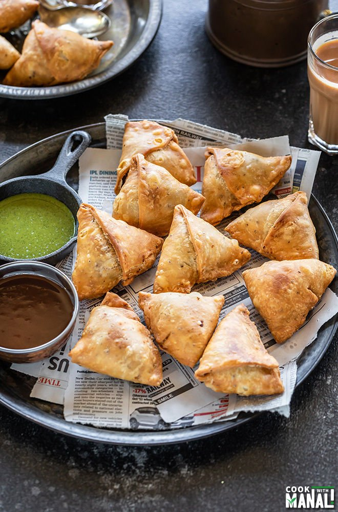 Fried samosa on top of newspaper with dipping sauces on the side