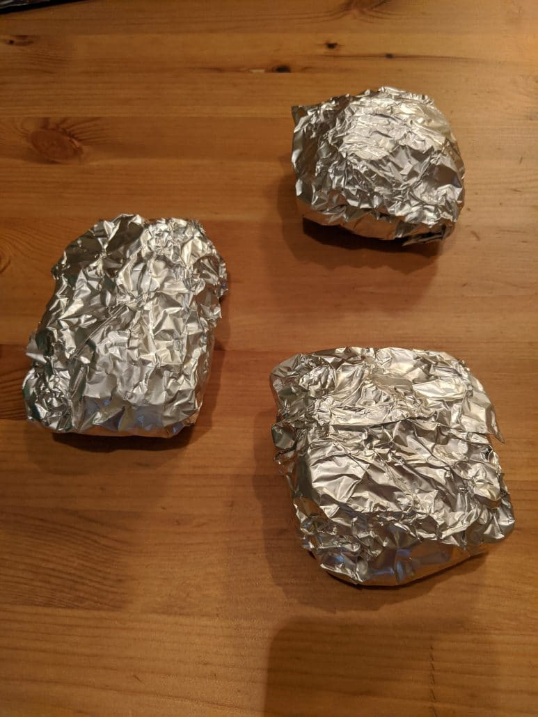 3 palusami rectangles wrapped in aluminum foil