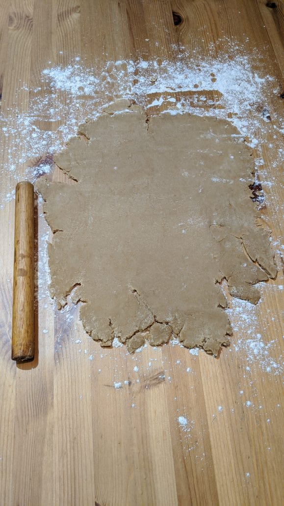 Fataya dough rolled out on a wood table