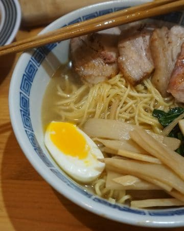 A bowl of shio ramen with bamboo shoot, spinach, pork, and egg