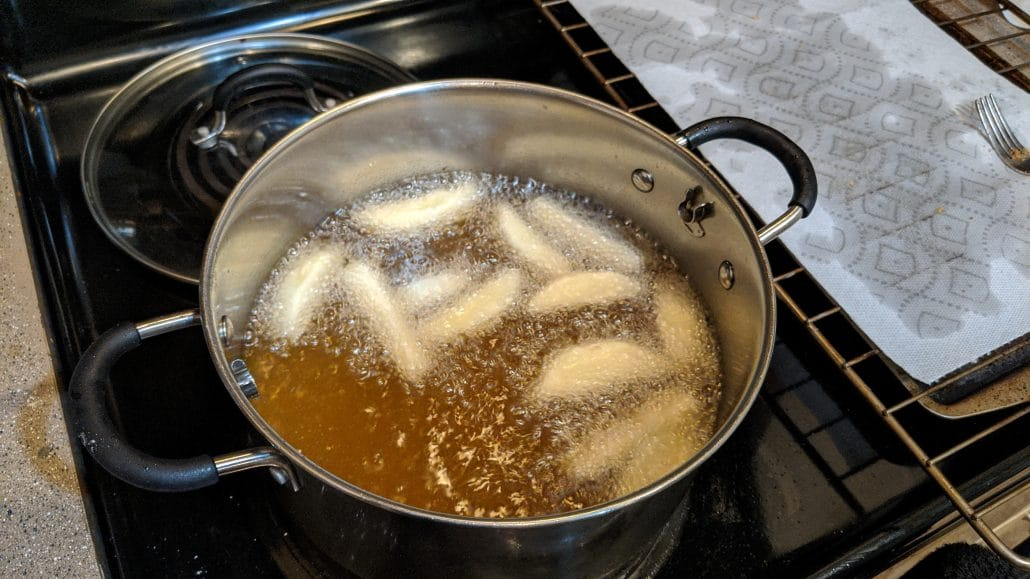 Apple slices frying in a pot of oil.