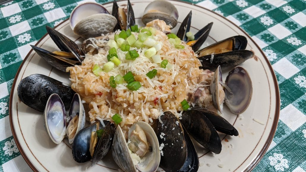 A plate of seafood risotto with red snapper, mussels, and clams