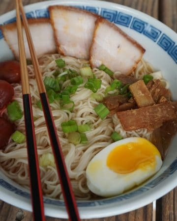 A bowl of Asahikawa ramen, with char siu pork belly, menma, green onion, softboiled egg, and pickled plums