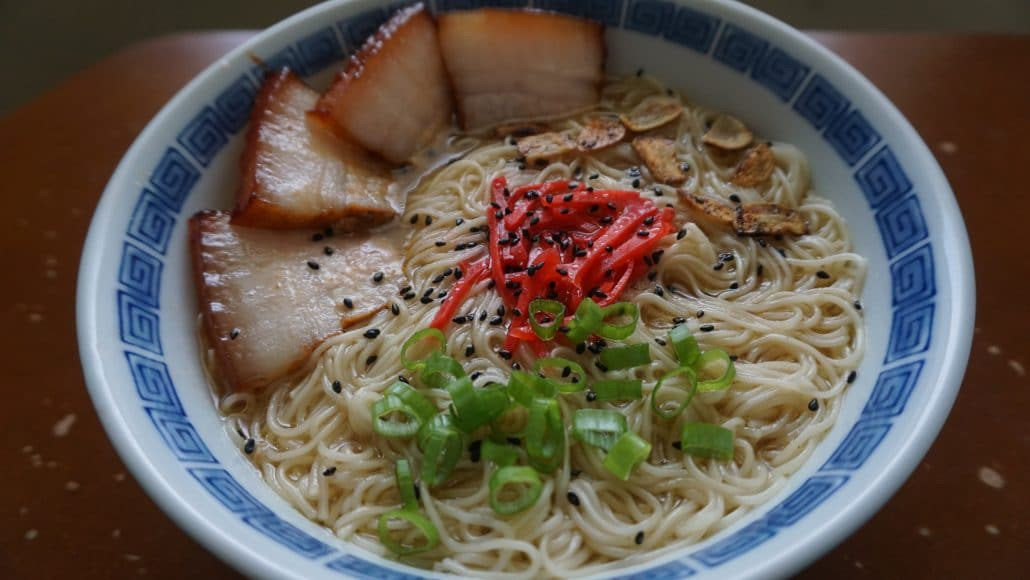 A bowl of hakata ramen with char siu pork belly, fried garlic, pickled ginger, green onion, and sesame seed toppings