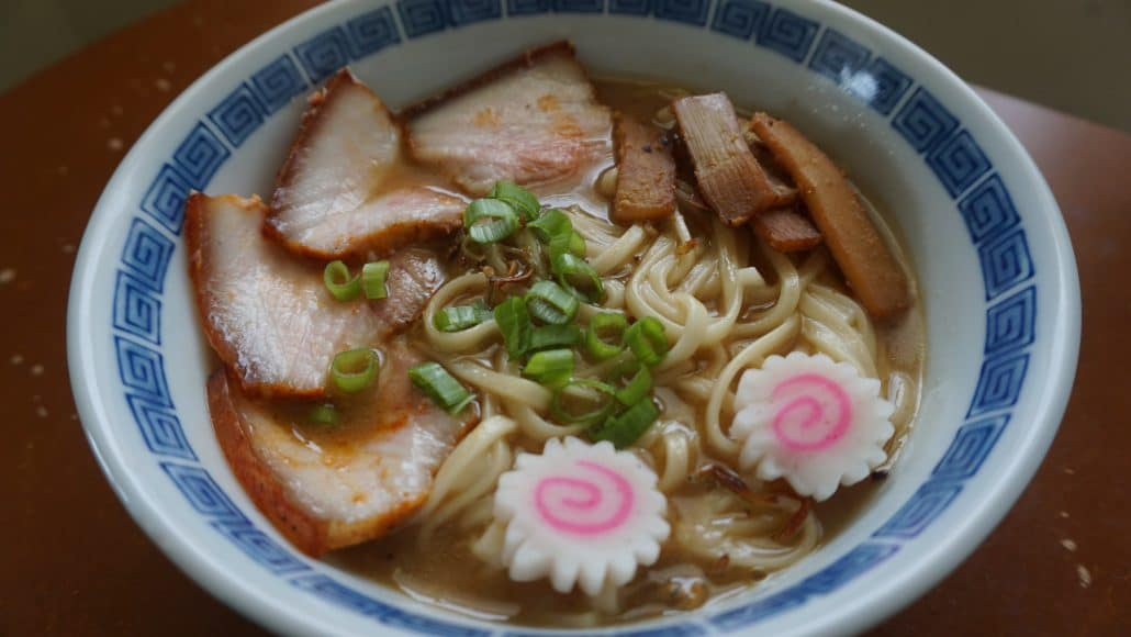 A bowl of Kitakata ramen with naruto fish cake, menma, scallions, and char siu pork belly.