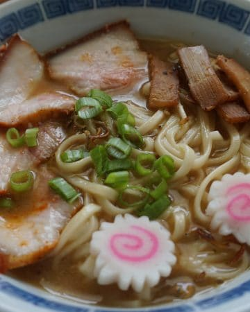 A bowl of Kitakata ramen, with naruto fish cake, scallions, menma, and char siu pork belly