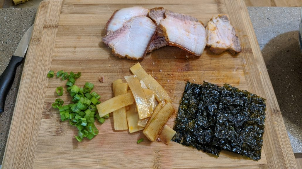 Kurume ramen toppings on a wooden cutting board