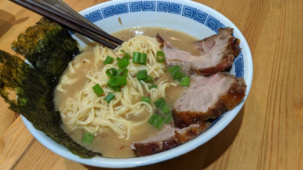 A bowl of miso ramen with scallions, seaweed, and chashu pork