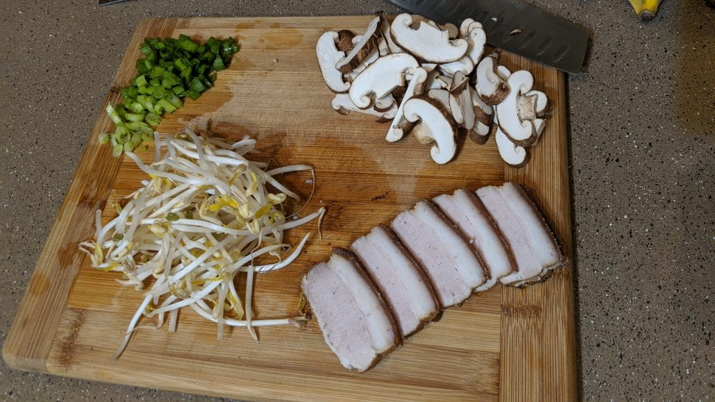 Scallions, bean sprouts, mushrooms, and pork belly on a cutting board