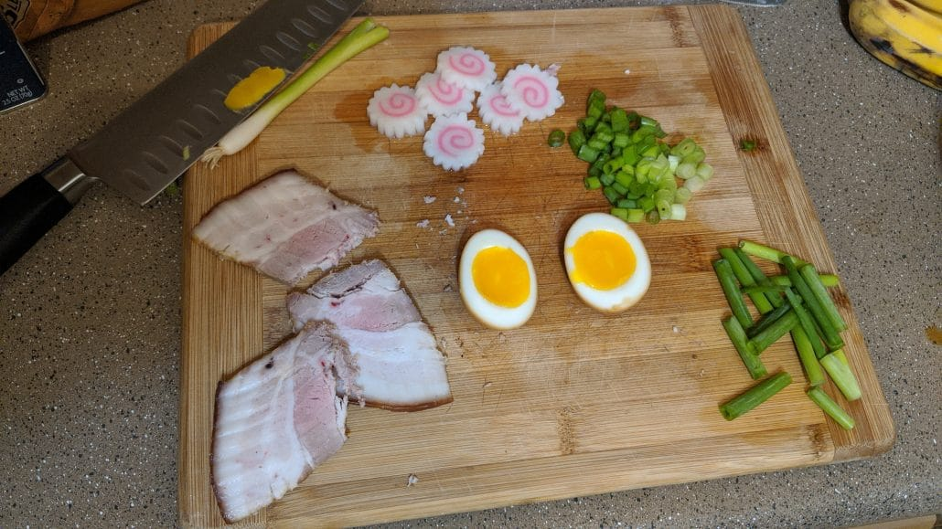 A cutting board with soft boiled egg, chashu pork slices, naruto fish cake, and sliced green onion