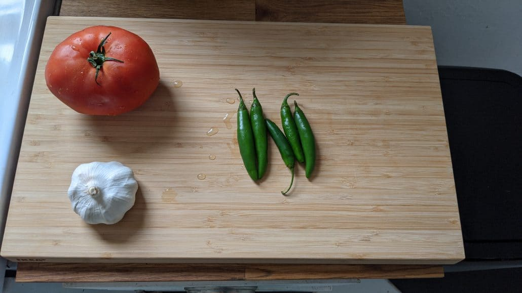 Tomato, garlic, and serrano peppers used in the harissa for this makloub recipe