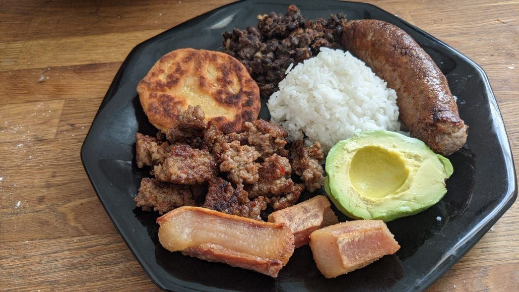 Bandeja paisa, a plate of rice, beans, sausage, arepas, avocado, and pork rinds