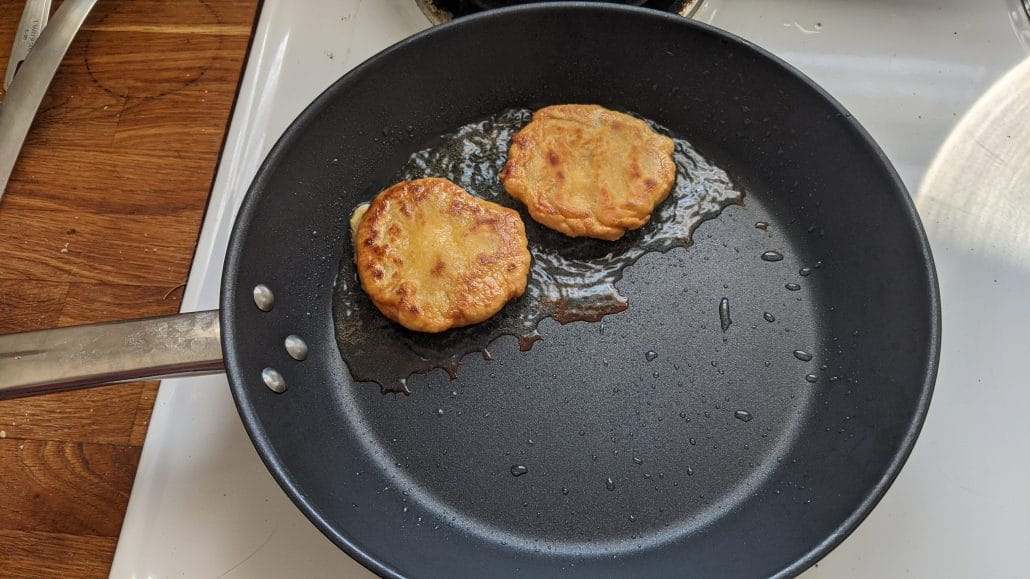 Frying arepas in a skillet for the bandeja paisa