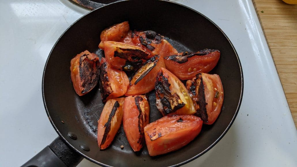 Charred tomatoes in a skillet