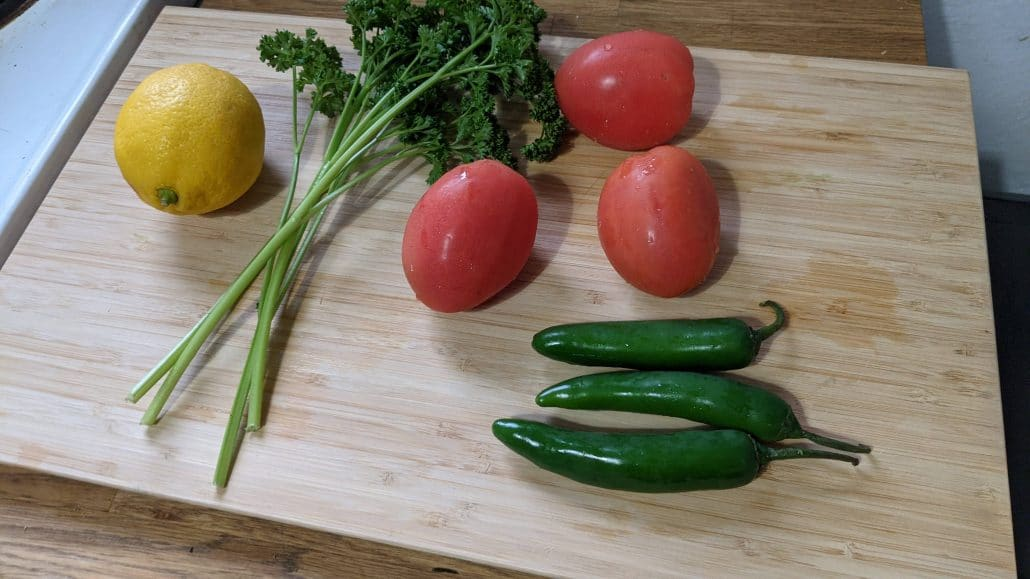 Chirmol ingredients including lemon, serrano peppers, roma tomatoes, and parsley.