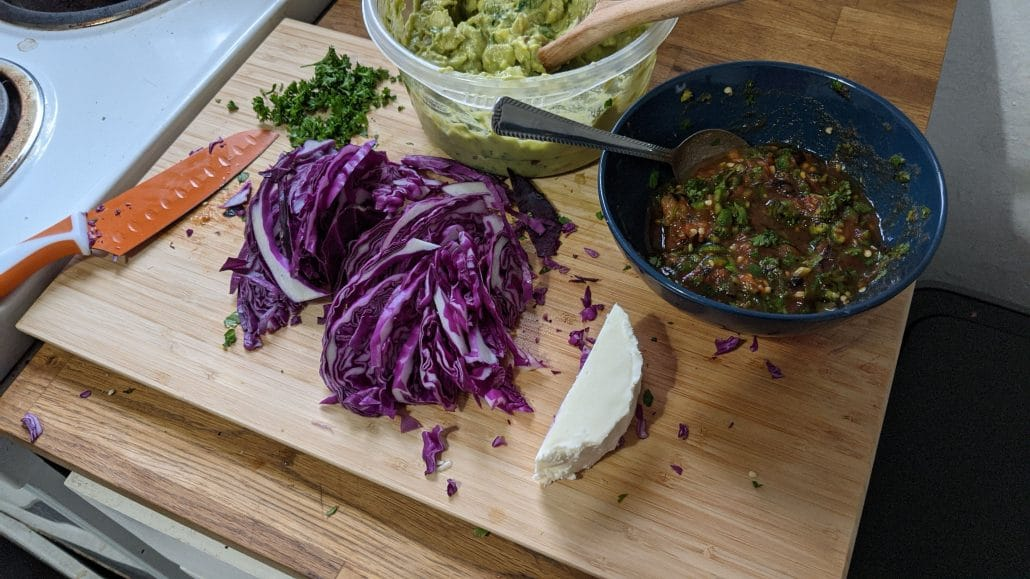 Toppings for the mixtas, including guacamole, queso fresco, chirmol, and red cabbage