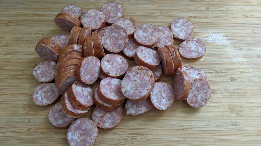 Sliced sausage, or salchipapas, on a cutting board